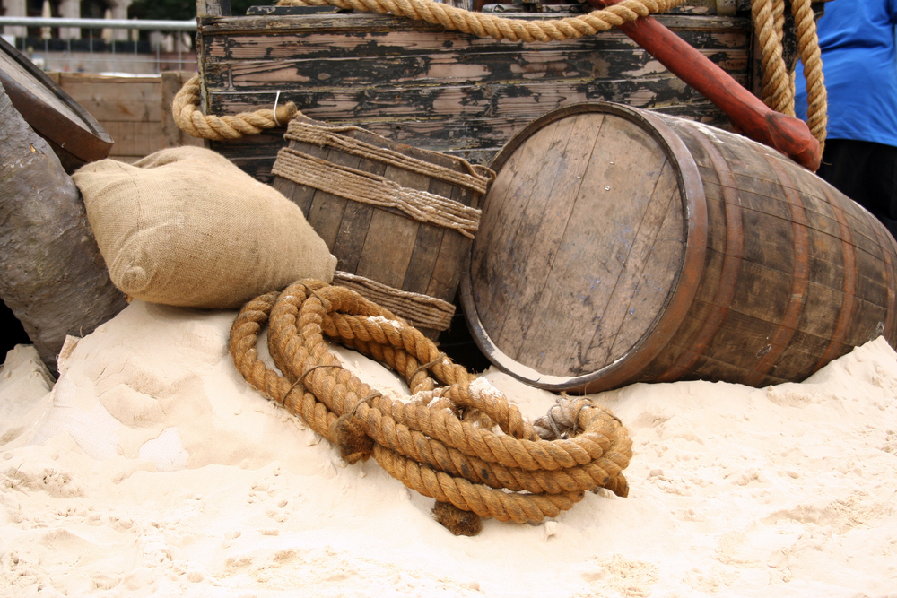 sandy beach with barrels and elements from a pirate boat